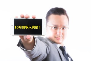iPhone6の画面(横)を見せるエンジニア (15.10)