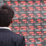 株価ボードを眺める男性